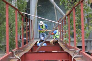 Metal Supply technicians installing railings and a red pedestrian bridge.